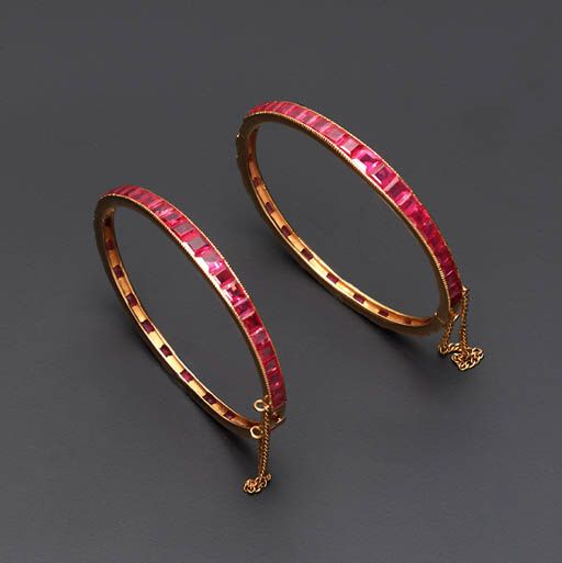 A pair of channel set ruby and gold bracelets.