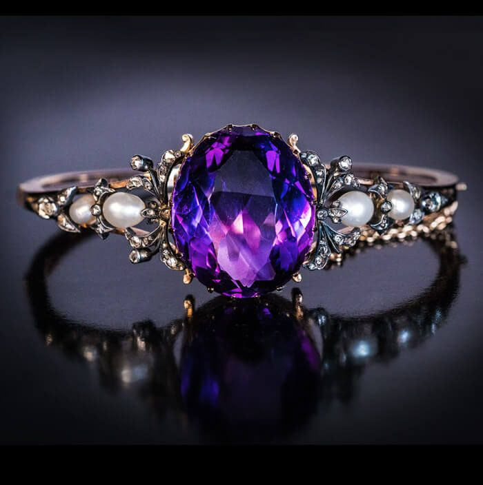 An antique 14K gold bangle bracelet features a 25.54 carat oval amethyst (likely...