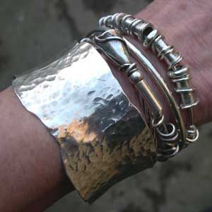 silver expanding bangles being worn with a cuff