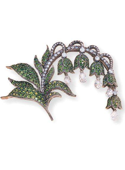 A TSAVORITE AND DIAMOND FLORAL BROOCH Designed as a series of tsavorite lilies, ...