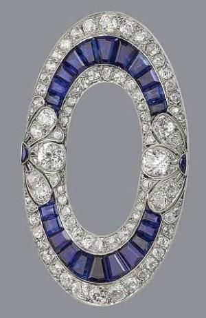 A sapphire and diamond brooch, circa 1915 The openwork ellipse set with calibré...