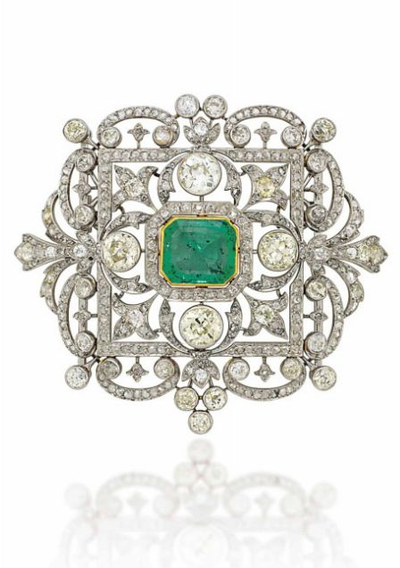 AN EARLY 20TH CENTURY EMERALD AND DIAMOND BROOCH/PENDANT The curved openwork car...