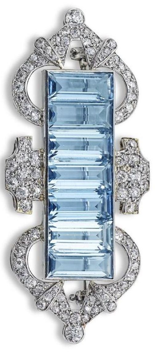 An Art Deco aquamarine and diamond brooch. Set with a row of baguette-cut aquama...