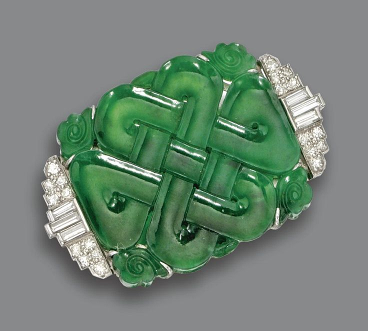 CARVED JADE AND DIAMOND BROOCH, CIRCA 1930.  The jade plaque carved with an intr...