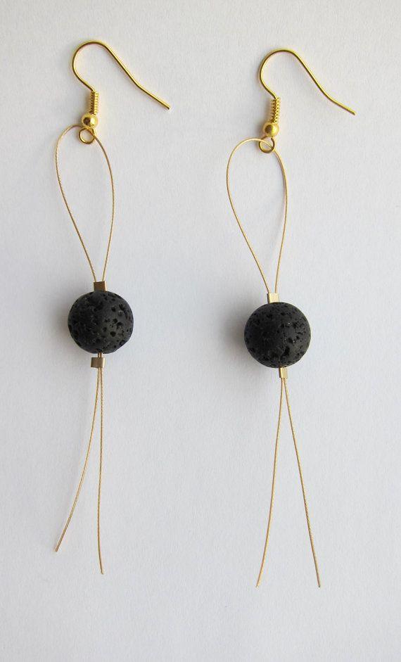 Pendientes de lava de un alambre dorado con ganchos de oreja de oro. Los pendien...