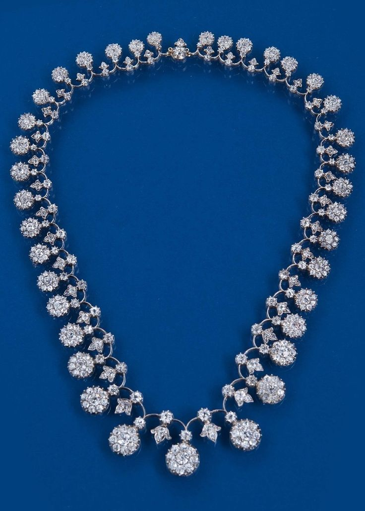 A VICTORIAN DIAMOND NECKLACE. Mounted with graduated diamond clusters and gradua...