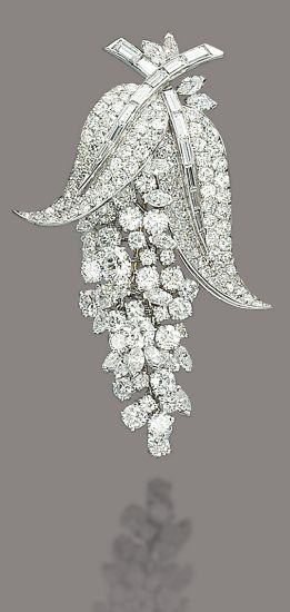 A DIAMOND BROOCH, BY MARCHAK. The brilliant-cut and marquise-shaped diamond flex...
