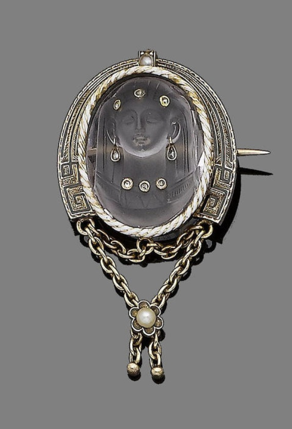 A rock crystal and diamond-set brooch  The oval rock crystal plaque carved to de...