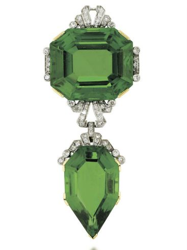 AN EARLY 20TH CENTURY PERIDOT AND DIAMOND BROOCH PENDANT. Cmposed of an octagona...