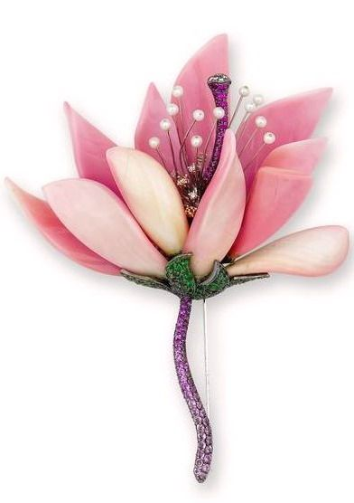 A gem-set brooch Designed as a flower, the petals composed of carved conch pearl...
