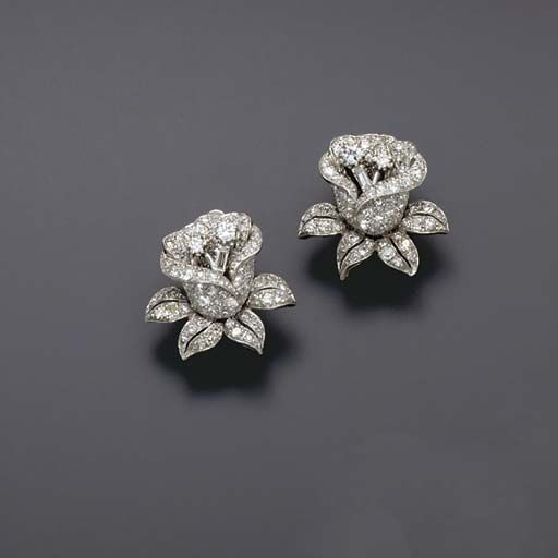 A pair of ear clips, each designed as a pavé-set diamond flower, to the baguett...