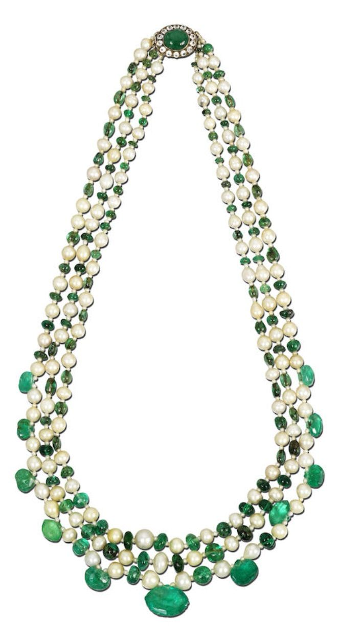 A vintage emerald and natural pearl necklace, circa 1930. The three rows compose...