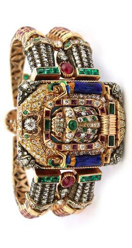 An Egyptian revival enameled, diamond, ruby and emerald set bangle, the rectangu...