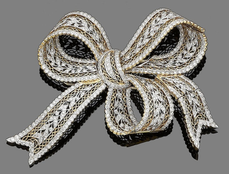 A diamond bow brooch Designed as a bow decorated with a garland of leaves, set t...