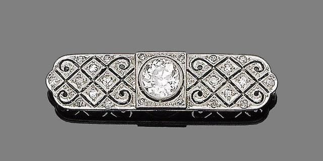 A diamond brooch, circa 1920 Centrally-set with a collet-set old brilliant-cut d...