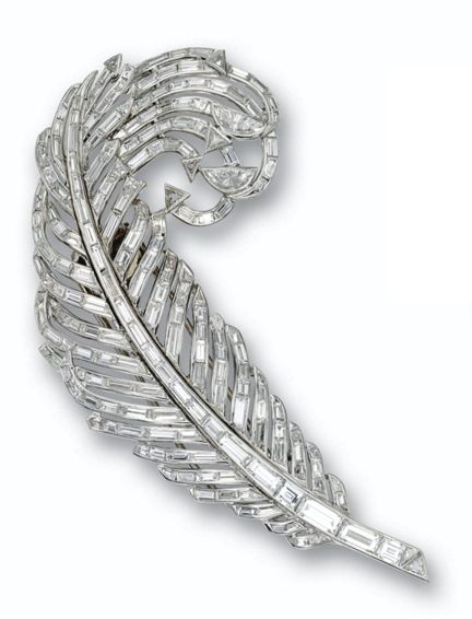 DIAMOND FEATHER BROOCH, CIRCA 1950 The curling feather set with numerous baguett...
