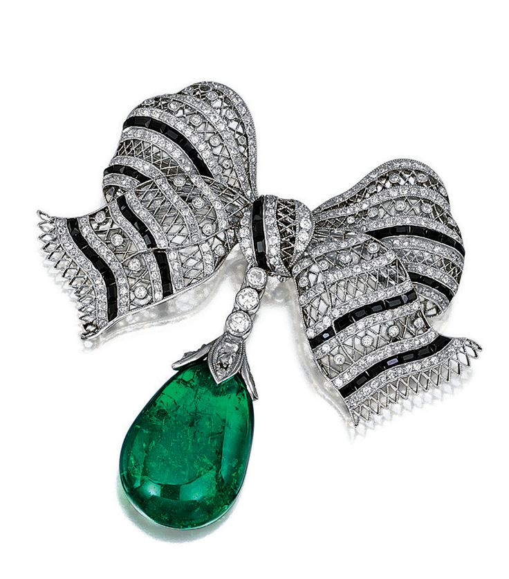 ONYX, EMERALD AND DIAMOND BROOCH.  Designed as a bow, set with single-, circular...
