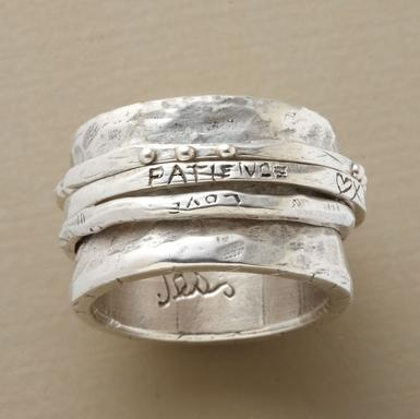 Three slender rings spin on a broad, hammered base band, one etched with