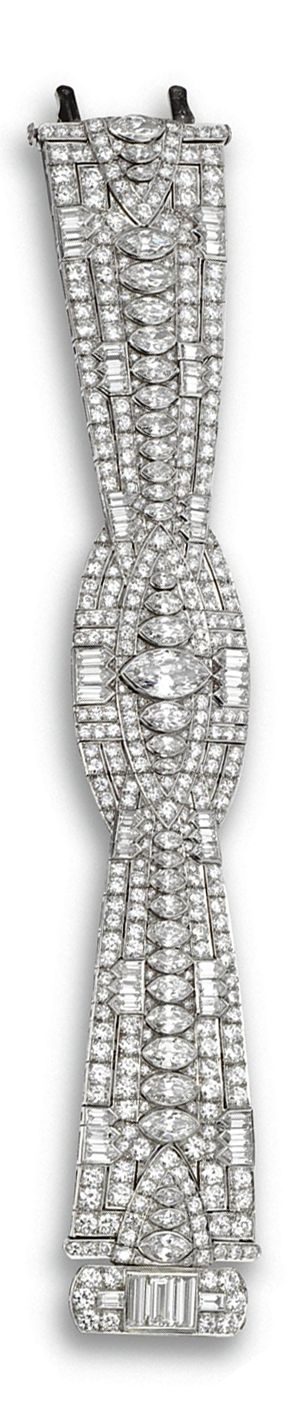 DIAMOND BRACELET, CIRCA 1930.  The central oval motif flanked by flared straps, ...