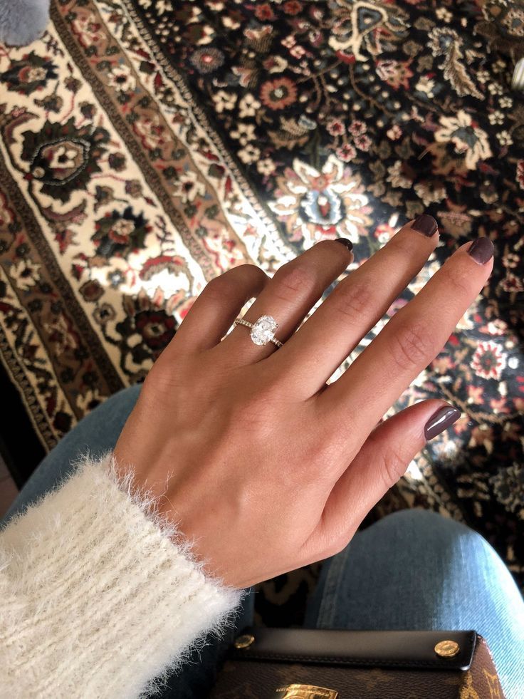 The perfect engagement ring. Oval diamond set in gold with a thin pave diamond b...