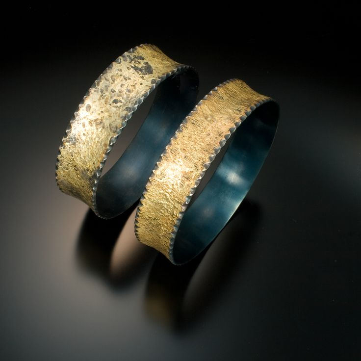 A pair of mild steel bangles, fused with 20K gold.