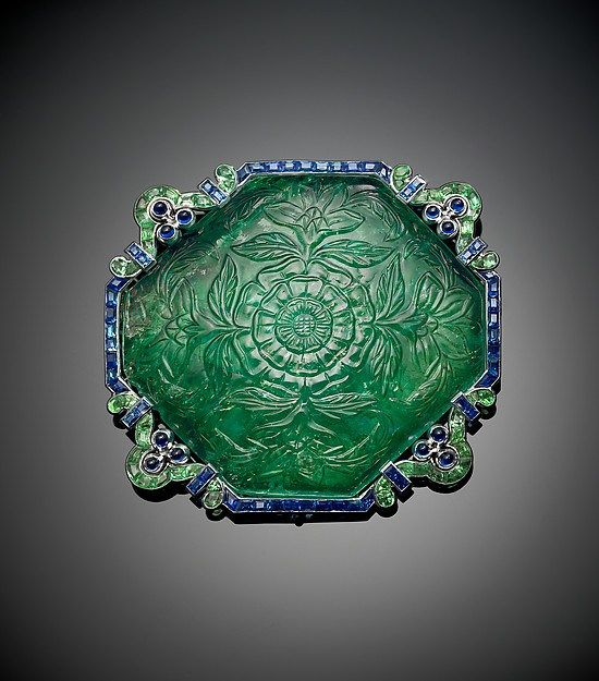 A brooch featuring a carved emerald bordered by calibré-cut emerald and sapphir...