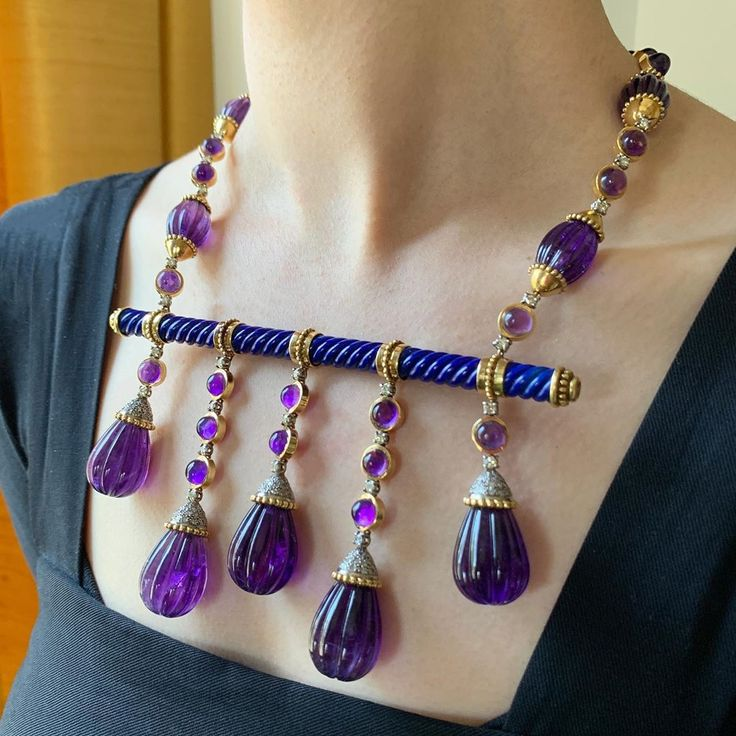 A regal necklace designed with carved amethyst briolettes and diamonds, suspende...