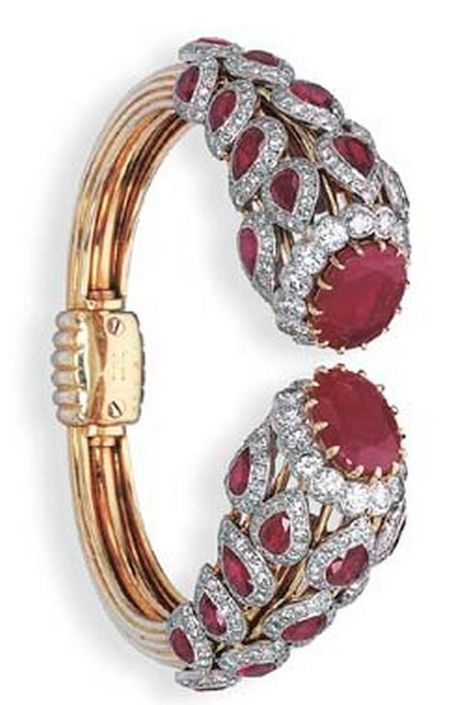 RUBY AND DIAMOND BANGLE, BY CARTIER Designed with oval-cut ruby and brilliant-cu...